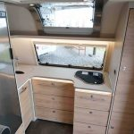 Keuken in Dethleffs Nomad 490 BLF met 142 liter koelkast, 3 pits gasstel en veel lichtinval.