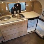 Keuken in Dethleffs caravan nomad 730 fkr. De keuken bevat veel opbergruimte, een koelkast en een 3pits gasstel
