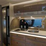 Keuken in de Nomad 650RQT. De keuken is voorzien van een 142 liter koelkast, een 3 pits gasstel en heel veel opbergruimte door de vele kasten.