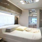 Het queensbed in de caravan. Achter het queensbed is de badkamer.