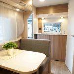 Overzichtsfoto C'joy 420. In het midden van de caravan bevindt zich een treinzit. Achterin de toiletruimte en het keukenblok.
